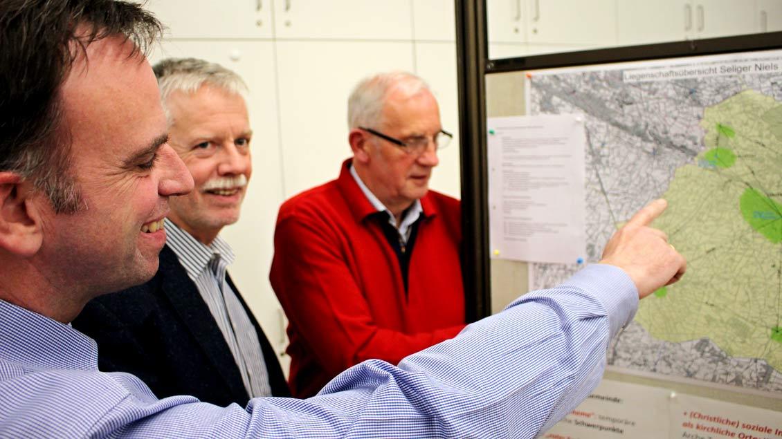 """Michael Schüller (vorne links), Alexander Fenker und Alois Thomes aus der Steuerungsgruppe """"Lokaler Pastoralplan"""" erklären die Landkarte der Pfarrgemeinde Seliger Niels Stensen."""
