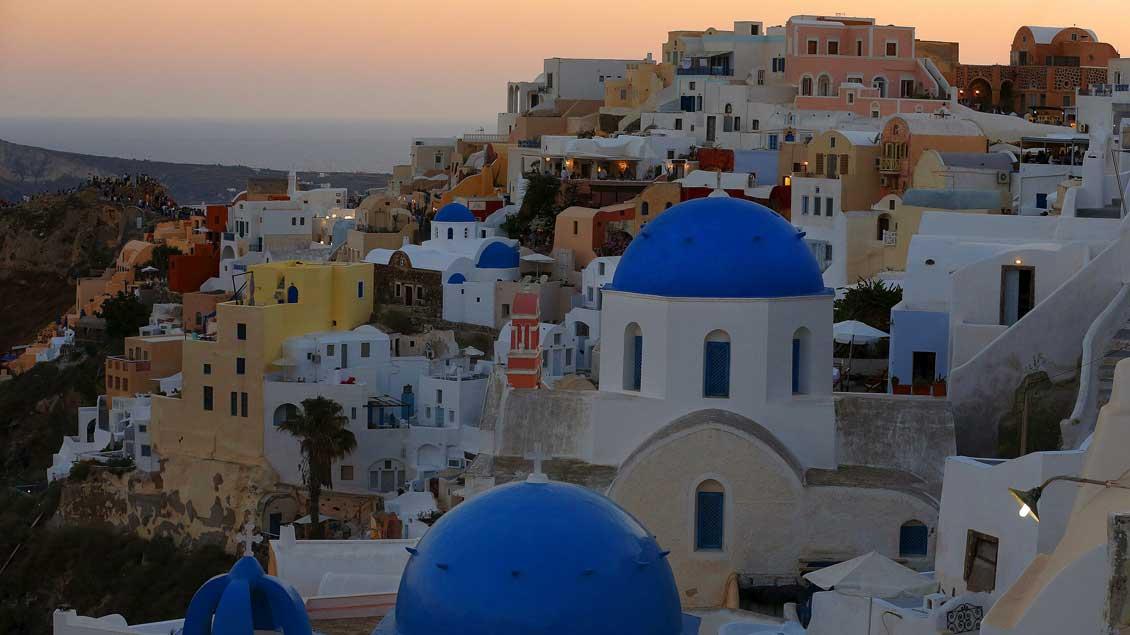 Sonnenuntergang über Santorin und den typischen Kirchen mit den blauen Kuppeln.