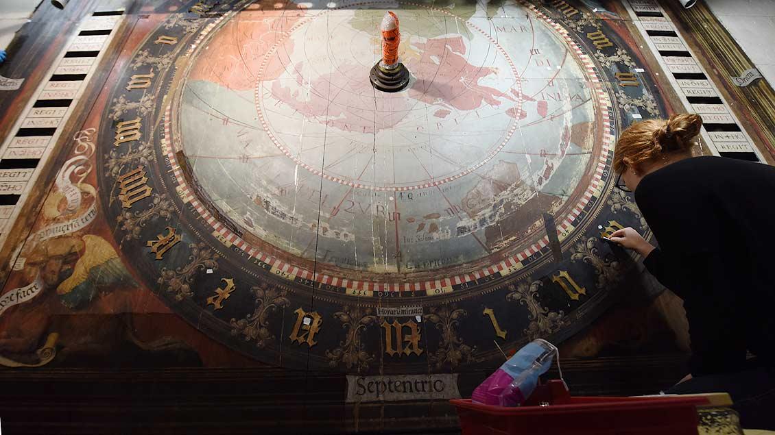 Millimeterarbeit am drei Meter hohen Ziffernblatt: Restauratorin Charlotte Hoffmann beschäftigt sich mit dem Zahlenkranz der Astronomischen Uhr. | Foto: Michael Bönte