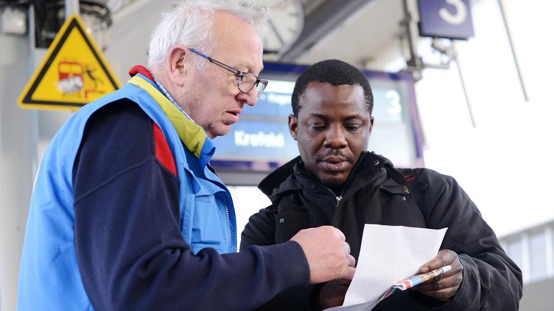 Ein ehrenamtlicher Mitarbeiter der münsterschen Bahnhofsmission hilft einem Reisenden bei der Weiterfahrt.