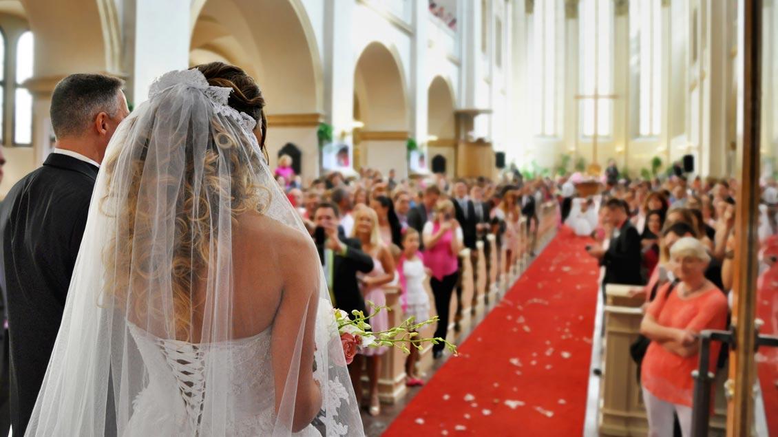 Ein Brautpaar zieht zur Trauung in eine Kirche ein.
