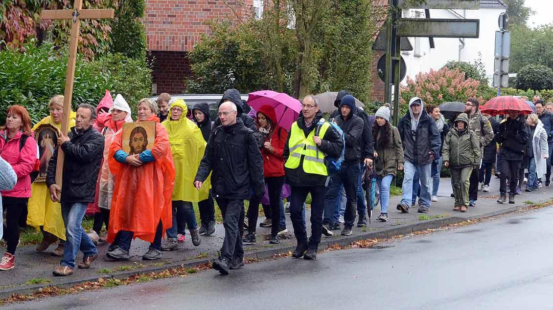 Mit Cape und Regenschirmen nach Telgte unterwegs: Die Pilger auf der internationalen Jugendwallfahrt aller Muttersprachler im Bistum Münster.