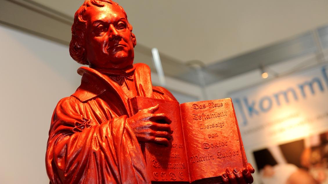 Eine Figur des Reformators Martin Luther (1483-1546) mit dem Neuen Testament in der Hand.