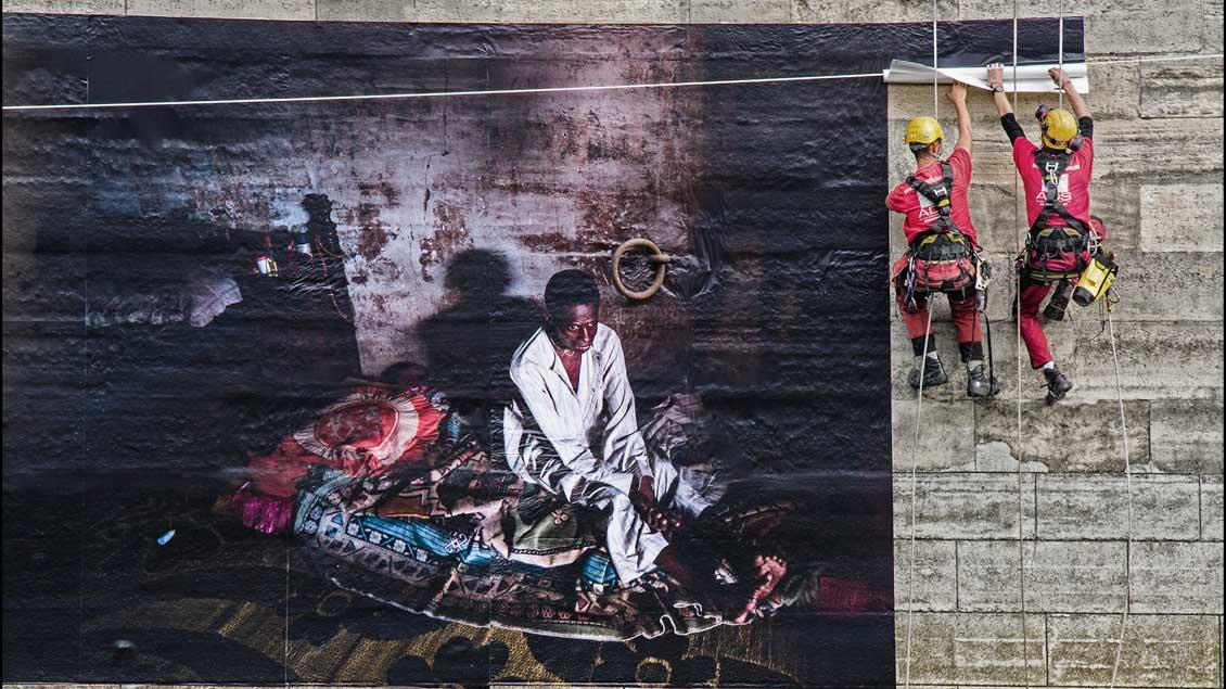 Das Foto von Rainer Döring zeigt ein Banner in Paris, auf dem die Situation eines Flüchtlings zu sehen ist. | Foto: Rainer Döring