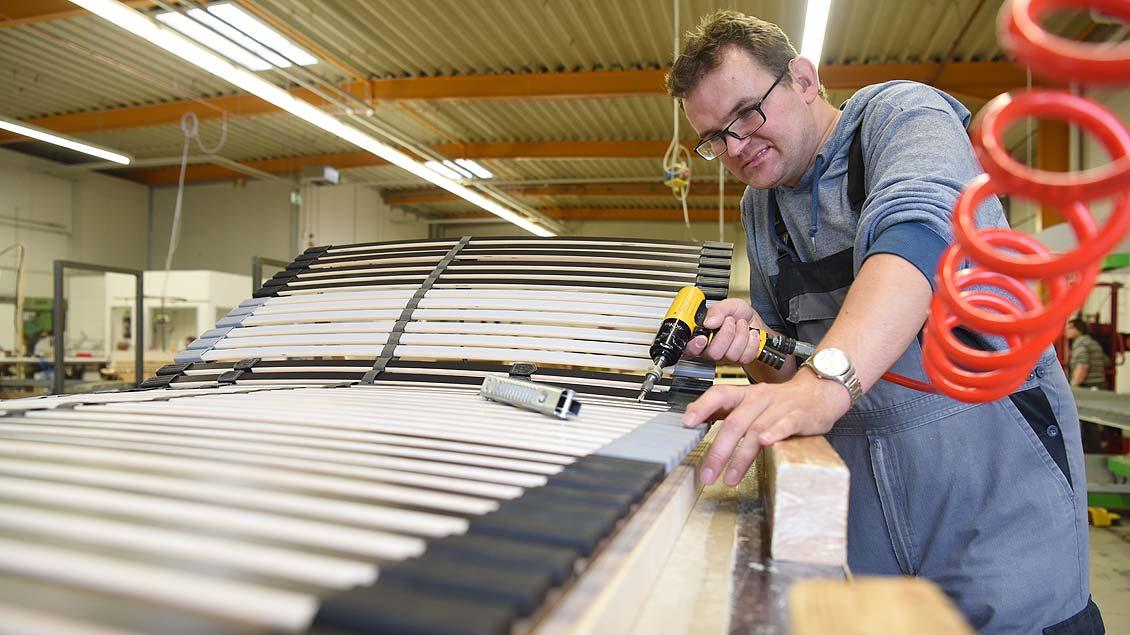 Roman Bouma bei der Montage eines Lattenrostes für ein großes Möbelhaus.
