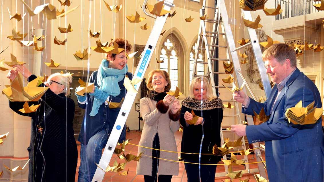 Künstlerin Ruth Blanke (2. von links) baut mit Rupert König (rechts) und den ehrenamtlichen Mitarbeiterinnen des Kirchenfoyers Karin Dame, Ursula Höing-Wegmann und Gabriele Sobke (von links) die Installation in der Überwasserkirche auf.
