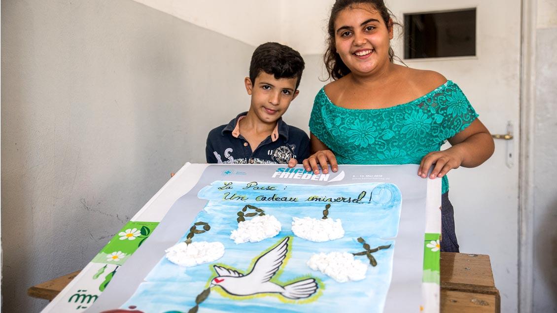 """""""Frieden - ein universelles Geschenk"""" steht auf dem Plakat dieser beiden syrischen Flüchtlingskinder."""