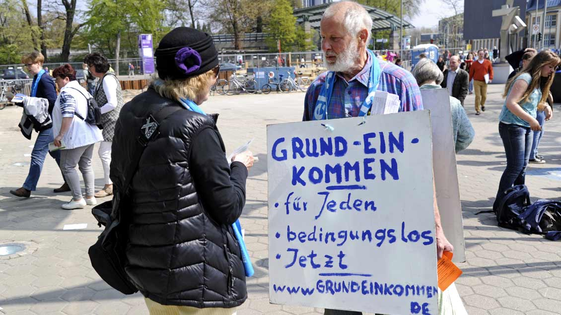 Ein Mann fordert mit einem Plakat die Einführung des bedingungslosen Grundeinkommens.
