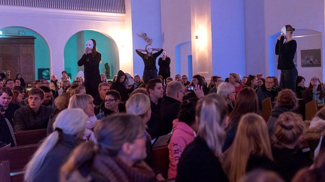 """o Aus der Gemeinde in der """"Klosterkirche"""" in Vechta erhoben sich Schülerinnen mit Masken ohne jede Mimik."""