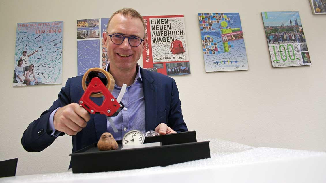 Einpacken, zum letzten Mal: Der scheidende Katholikentags-Geschäftsführer Martin Stauch wickelt persönliche Büro-Utensilien in Luftpolsterfolie ein.