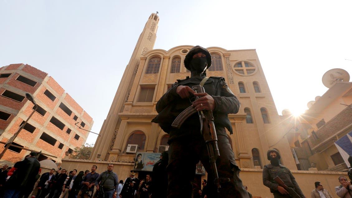 Sicherheitsbeamte stehen vor der Mar-Mina-Kirche in Helwan im Süden Kairos, auf die am Freitag ein Anschlag verübt wurde. Dabei sind mindestens neun Menschen getötet worden.