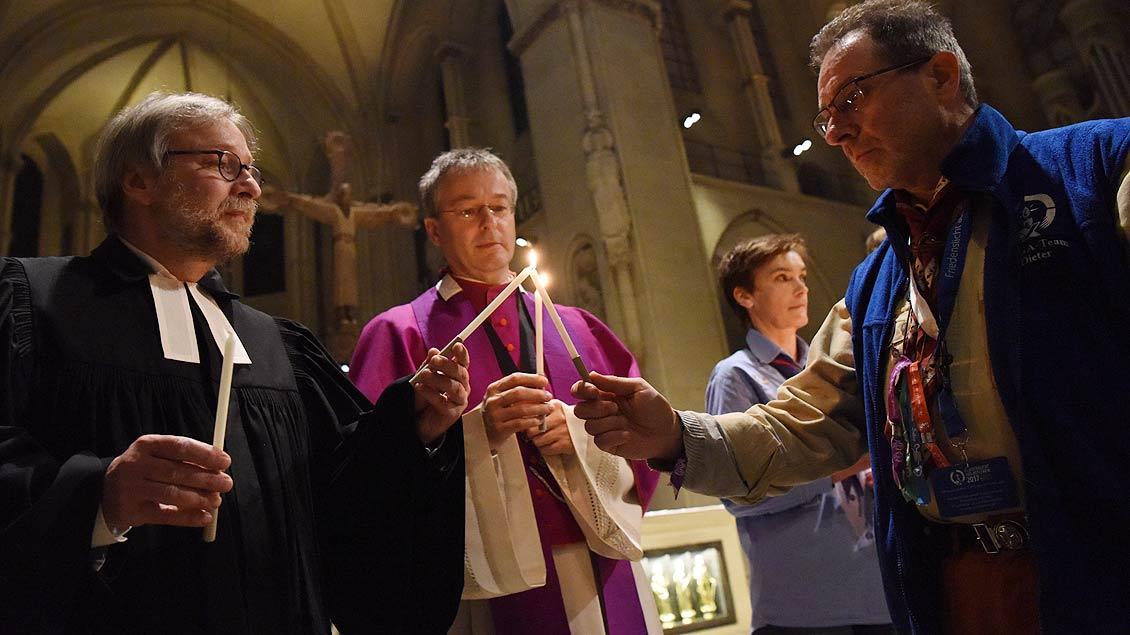 Der evangelische Pfarrer Martin Mustroph und Generalvikar Norbert Köster entzünden ihre Kerzen. | Foto: Michael Bönte