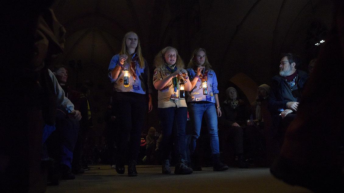 Drei Pfadfinderinnen bringen die Flamme mit ihren Kerzen zu Beginn des Gottesdienstes in den St.-Paulus-Dom. | Foto: Michael Bönte