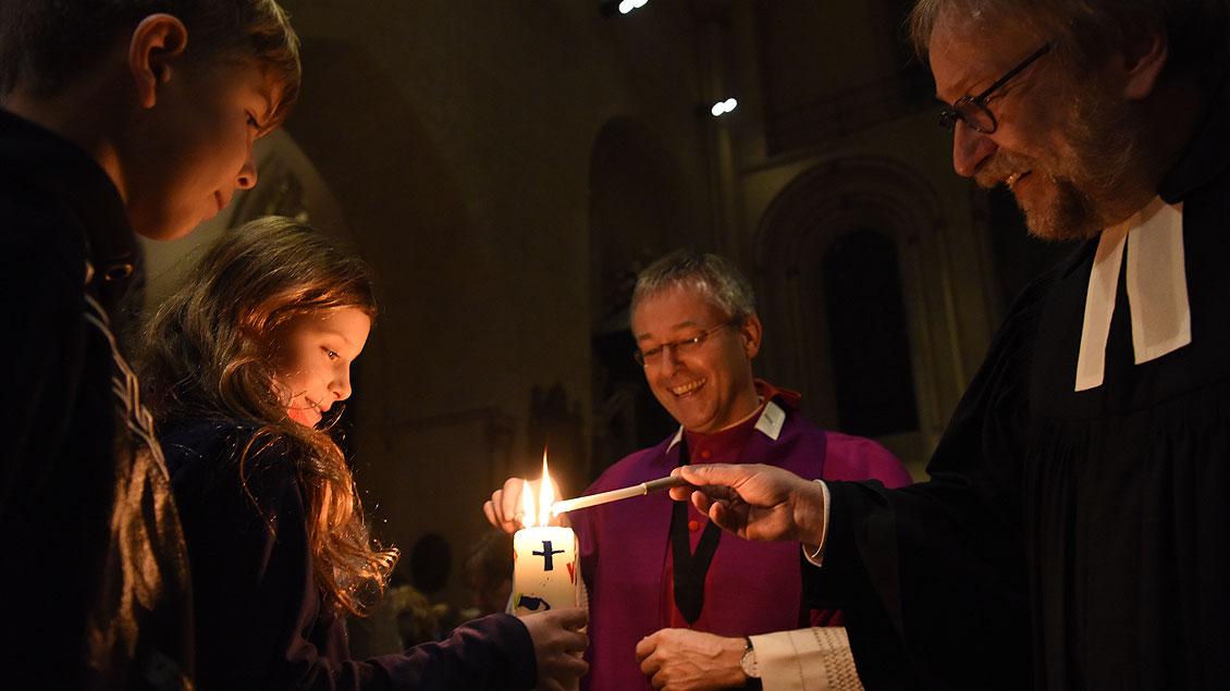 Der evangelische Pfarrer Martin Mustroph und Generalvikar Norbert Köster reichen die Friedens-Flamme an eine junge Frau weiter. | Foto: Michael Bönte