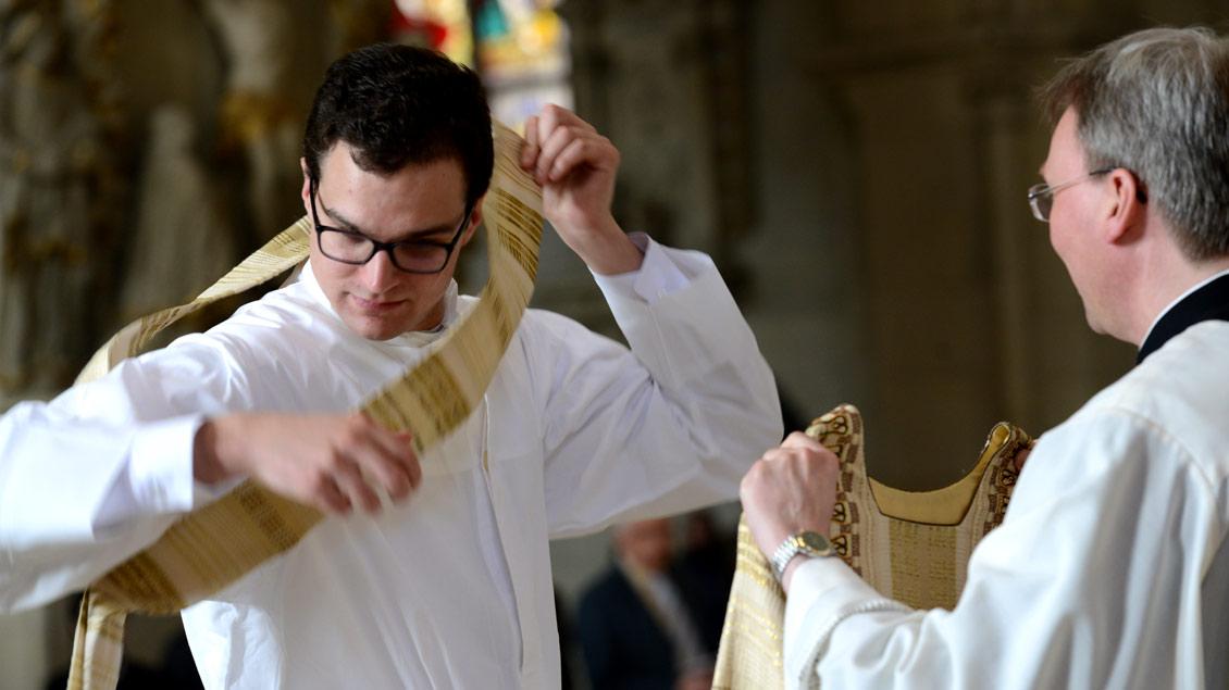 Während der Diakonenweihe legt der Kandidat die Querstola des Diakons an und empfängt die Dalmatik, die er über der weißen Albe trägt.