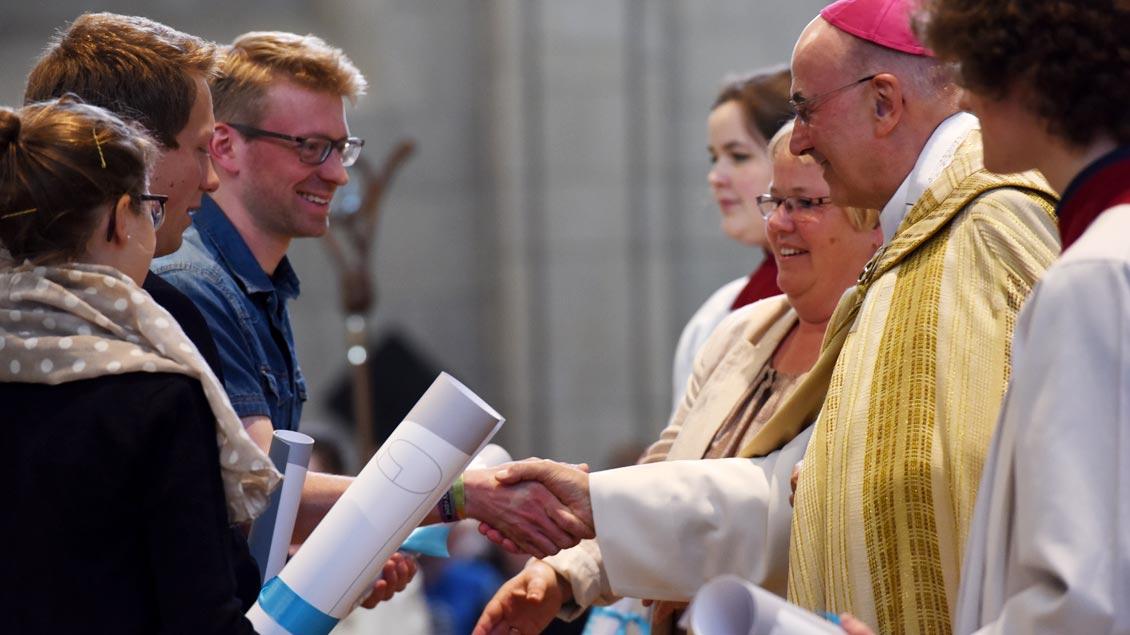 """Bischof Genn überreicht während der """"Aufklang""""-Veranstaltung zum Katholikentag im Mai 2017 leere Friedensverträge an Menschen aus dem Bistum."""