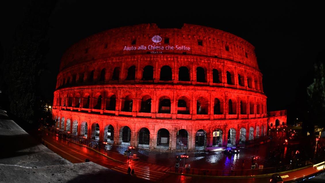 """Das Kolosseum in Rom wurde in Erinnerung an verfolgte Christen mit blutrotem Licht angeleuchtet und mit dem Schriftzug von """"Kirche in Not Italien"""" angestrahlt."""