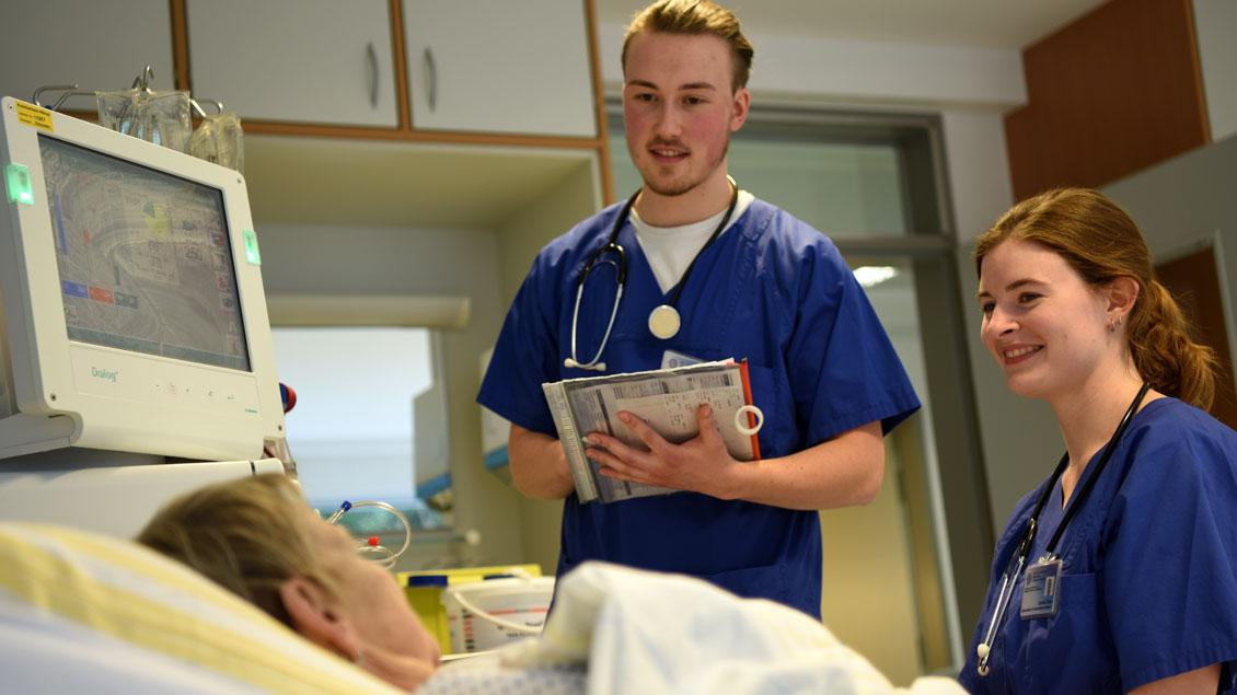 Leonie Stein und Simon Koch am Bett einer Dialyse-Patientin im Herz-Jesu-Krankenhaus in Münster-Hiltrup.