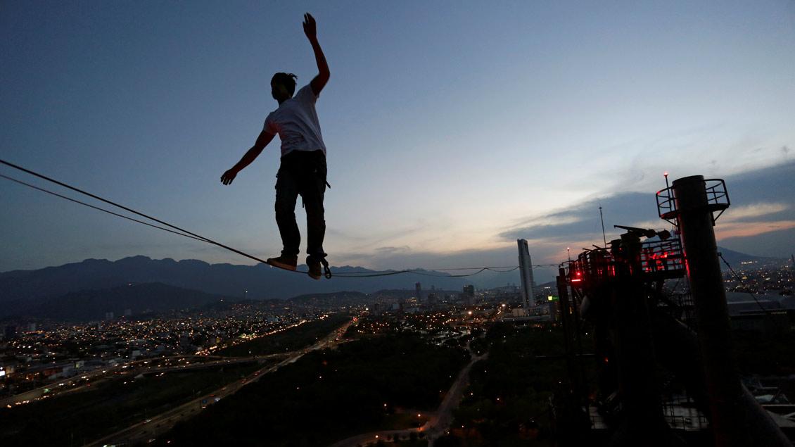 Ein Slackliner balanciert auf einem Hochseil zwischen zwei Schornsteinen im mexikanischen Monterrey.