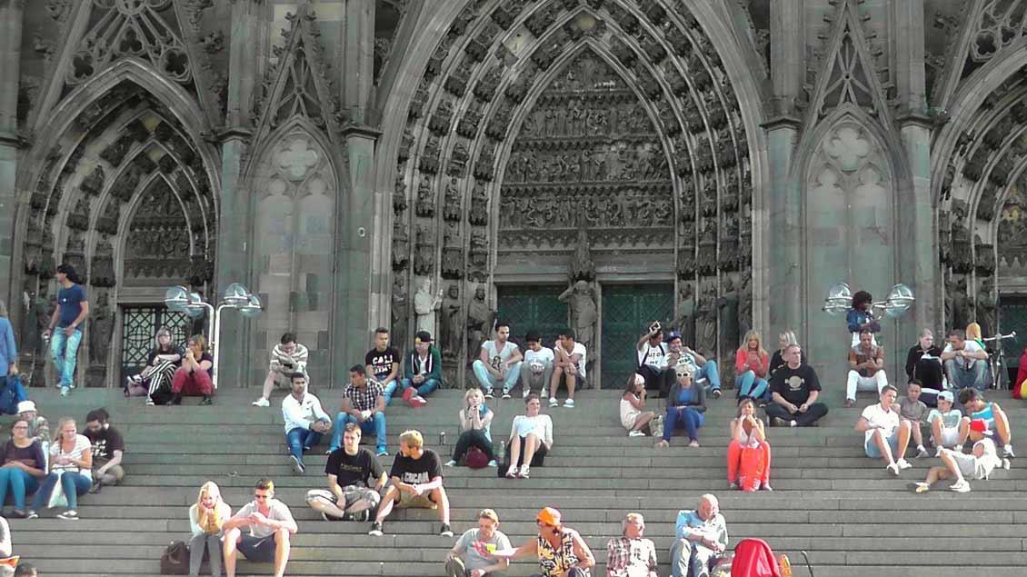 Menschen sitzen auf den Treppenstufen vor dem Kölner Dom.