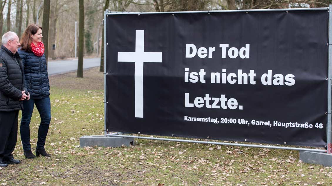 Pfarrer Paul Horst und Michaela Möllmann vom Pfarreirat an einem der Plakate.