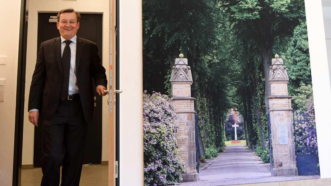 Ralf Hammecke im Foyer des neuen Gebäudes, in dem ein Foto der sommerlichen Friedhofsallee hängt.