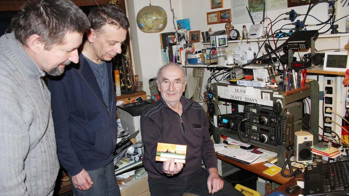 Diethard Klinkenberg (rechts) aus Münster-Nienberge zeigt an seiner Funkstation den Amateurfunkern Christian Reichert (links) und Thomas Groppe eine QSL-Karte. Mit dem Versand einer QSL-Karte bestätigen Funkamateure eine erfolgreiche Funkverbindung.