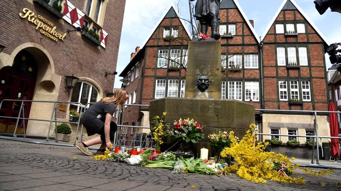 """Schweigend legen Menschen dem Tatort des Amoklaufs Blumen nieder, entzünden Kerzen: einem kleinen Platz vor der Traditions-Gaststätte """"Kiepenkerl""""."""