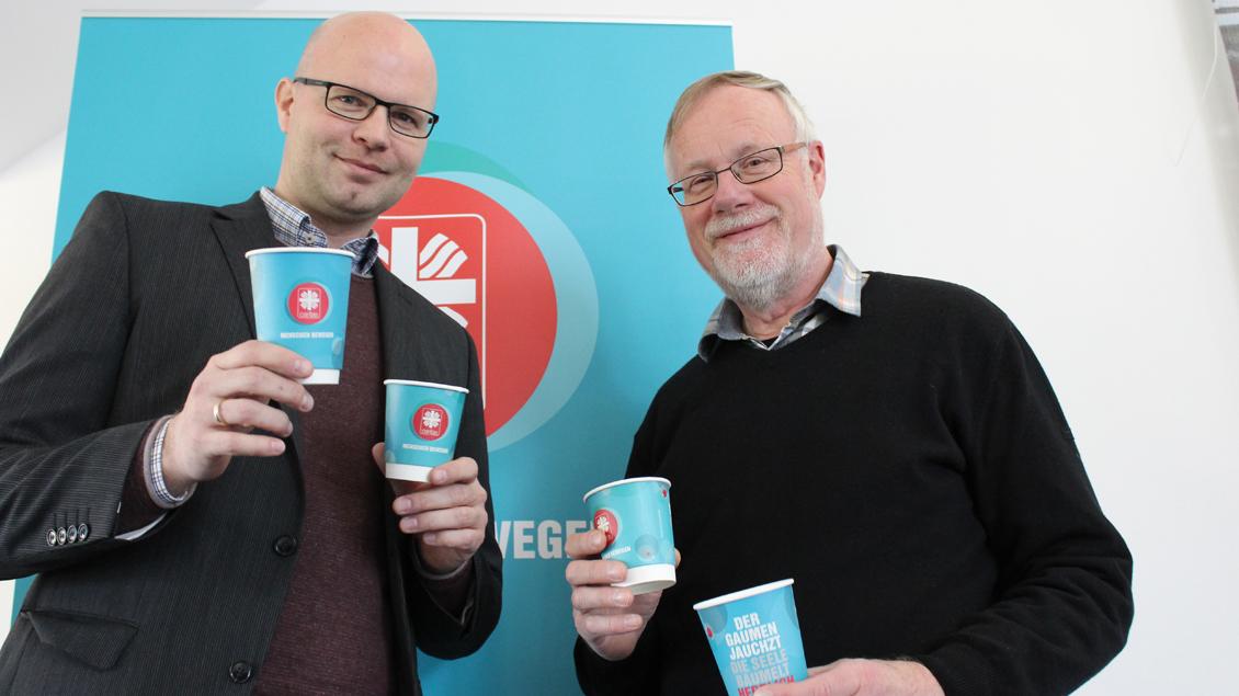 Der theologische Referent Boris Krause und Pressereferent Harald Westbeld (rechts) präsentieren die Kaffeebecher, die die Caritas für den Katholikentag bereit hält.