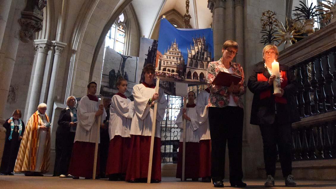 Prozession durch den Münsteraner Dom, angeführt von der Friedenskerze der Katholischen Frauengemeinschaft Deutschlands (KFD), die seit 1956 in einer Kapelle des Doms täglich brennt. | Foto: Michael Bönte