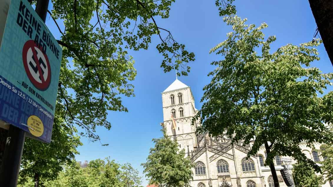 Schon vor dem Katholikentag in Münster hat der Auftritt des AfD-Politikers Volker Münz für Widerstand gesorgt, wie dieses Plakat auf dem Domplatz zeigt.