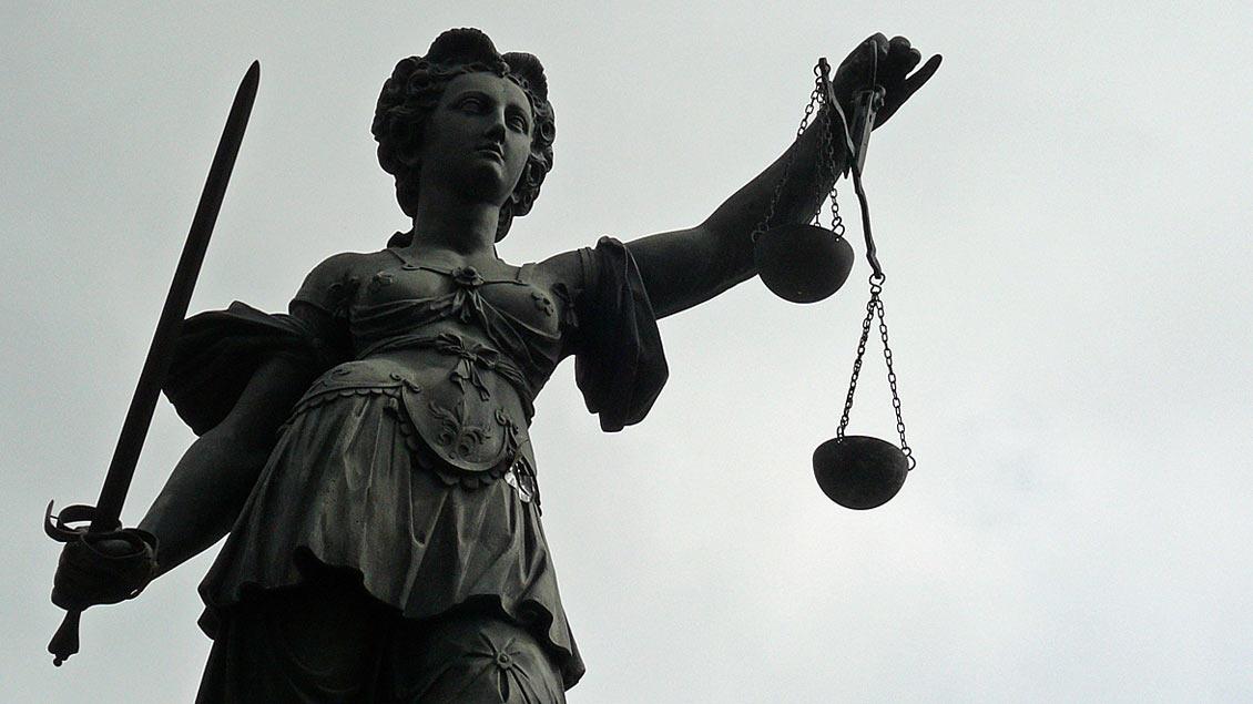Justitia, dargestellt mit Schwert und Waage.