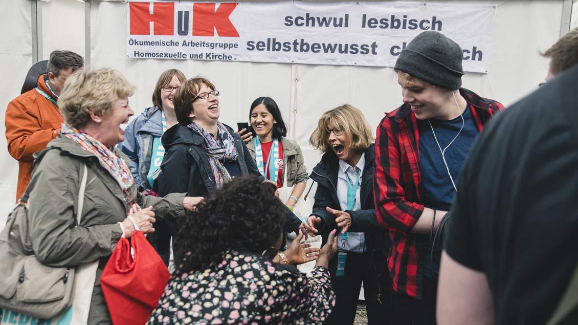 """Katholikentagsgäste vor dem Stand der ökumenischen Initiative """"Homosexuelle und Kirche""""."""