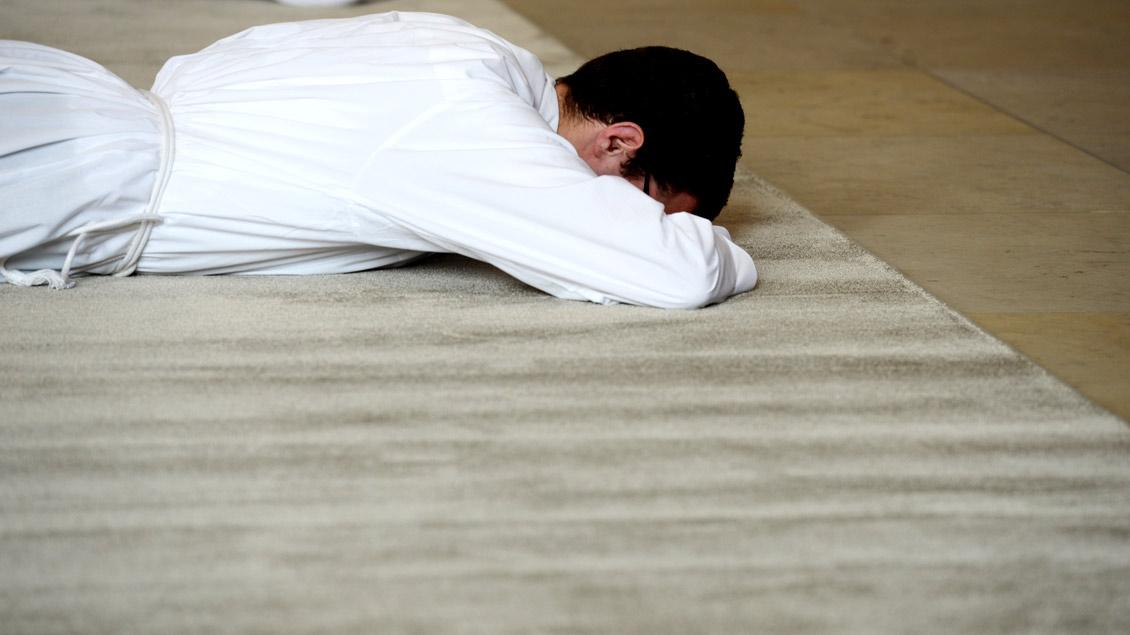 Ein Priesterkandidat liegt während der Weihe betend auf dem Boden.