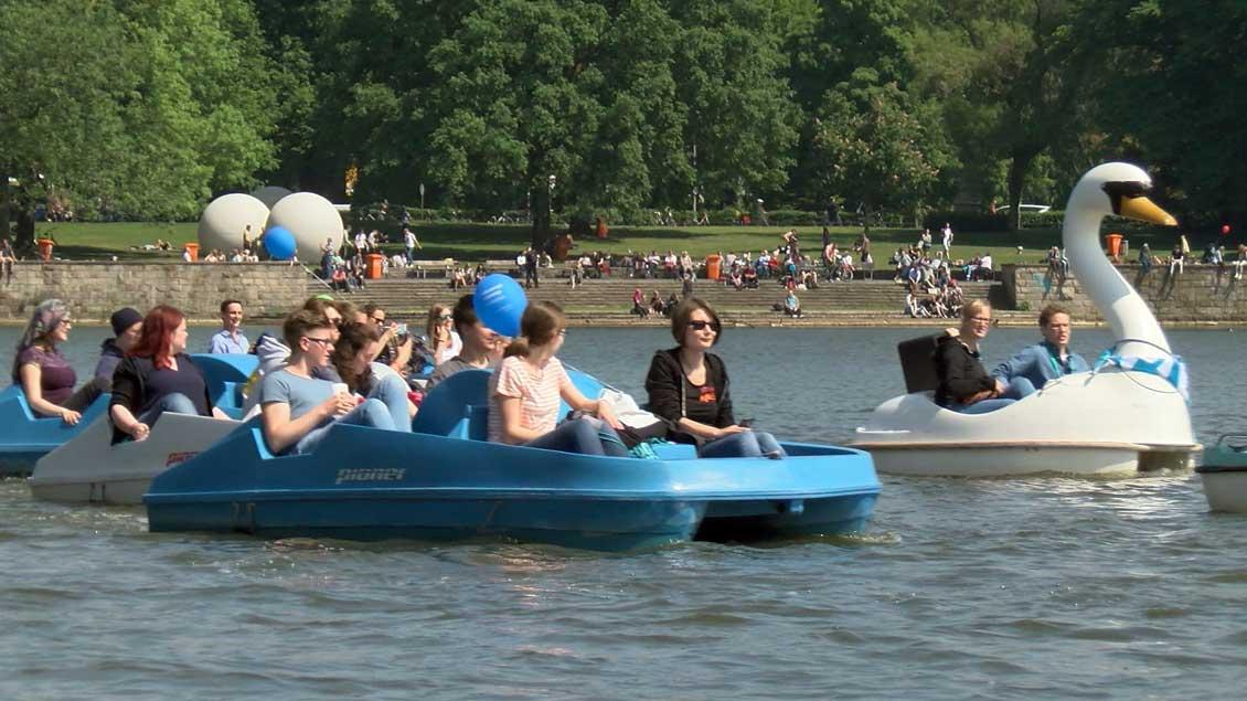 Der Schwan mit Katholikentagsschal schwamm auch mit beim ersten Tretbootgottesdienst auf Münsters Aasee.