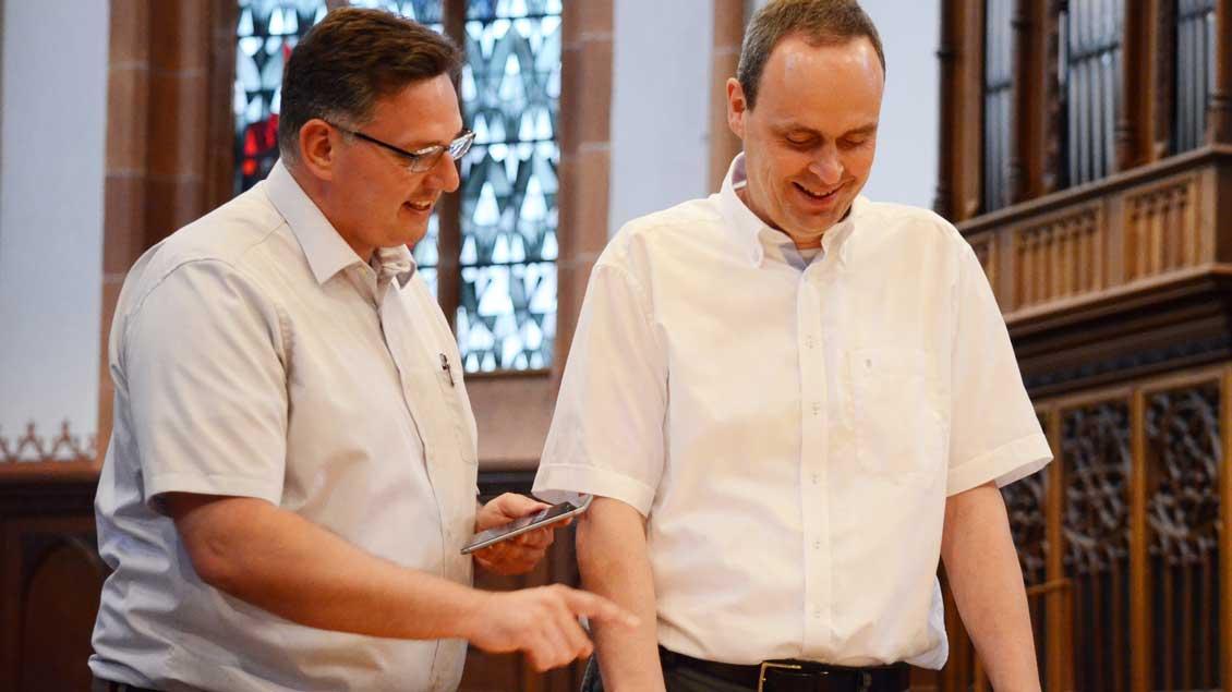 Proben für den Fernsehgottesdienst am 24. Juni aus Borken: Mit der Stoppuhr prüft Pater Lukas Rüdiger (links), wie viel Zeit Propst Christoph Rensing für das Tagesgebet braucht.
