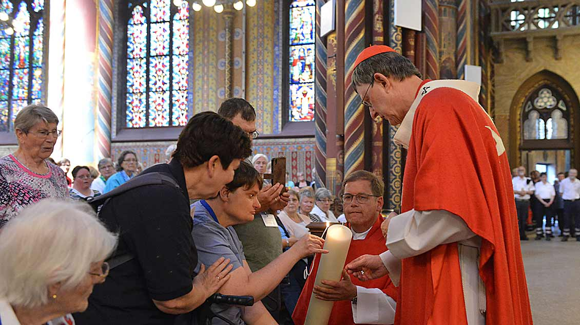 Kardinal Rainer Maria Woelki und Malteser Diözesanseelsorger Pfarrer Markus Polders entzünden gemeinsam mit einer Pilgerin die Kerze.
