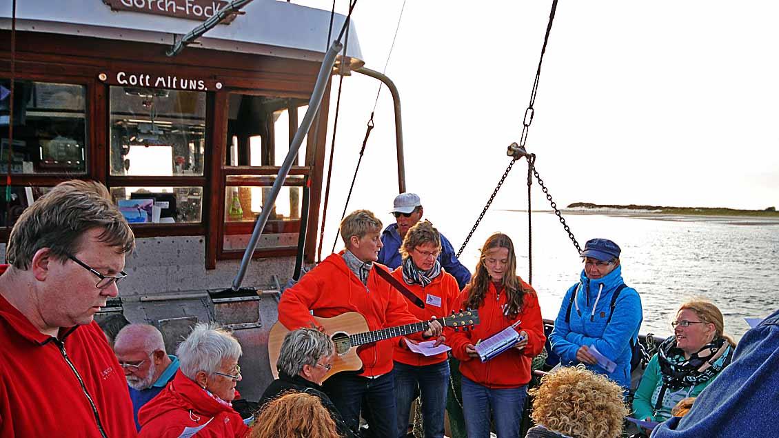 """Urlauberseelsorgerin Heike Pendias (mit Gitarre) feiert zusammen mit 50 Urlaubern im Windschatten der Insel Spiekeroog an Bord des Krabbenkutters """"Gorch Fock"""" eine Abendandacht."""