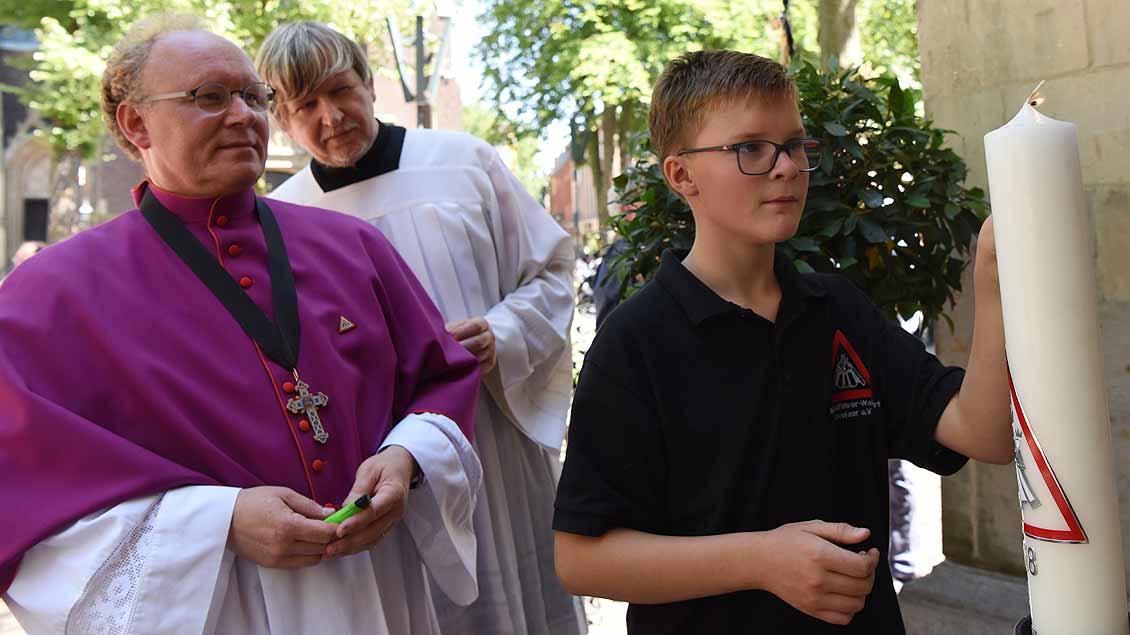 Jede Wallfahrt wird ein neue Kerze entzündet. Wallfahrtsrektor Pfarrer Georg Kauling mit einem Biker-Sohn. | Foto: Michael Bönte