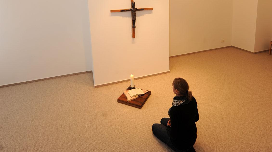Gebet vor einem Kreuz