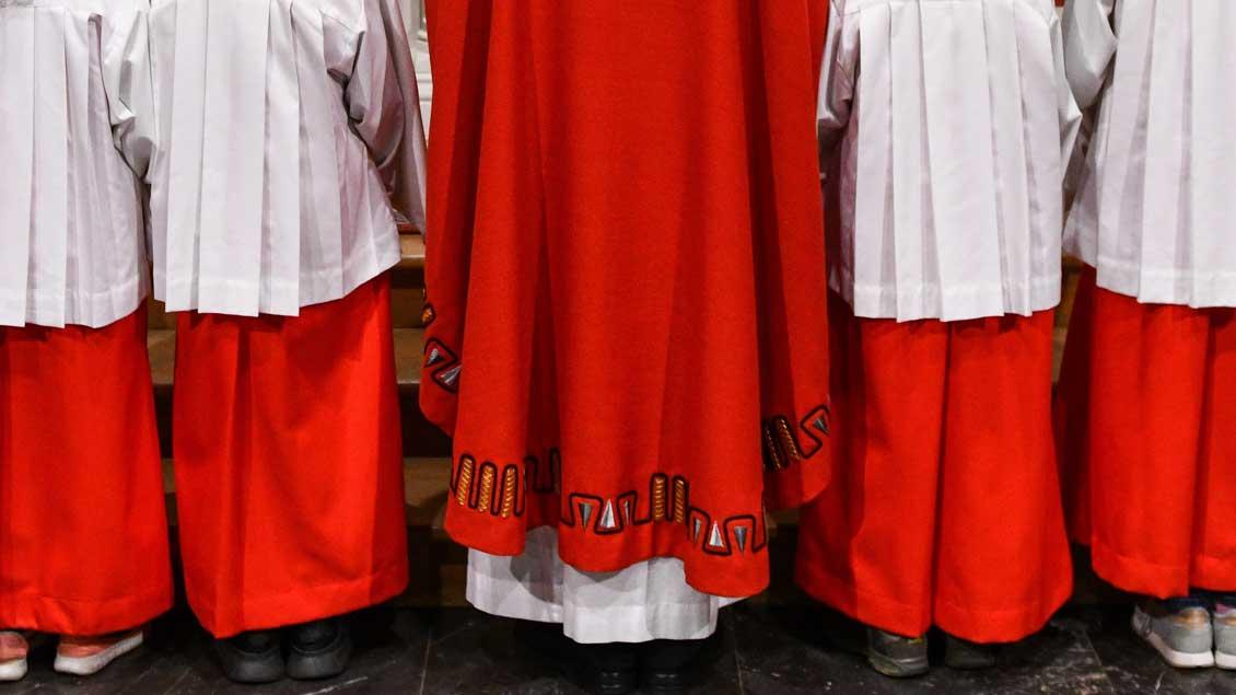 Messdiener und Priester am Altar.