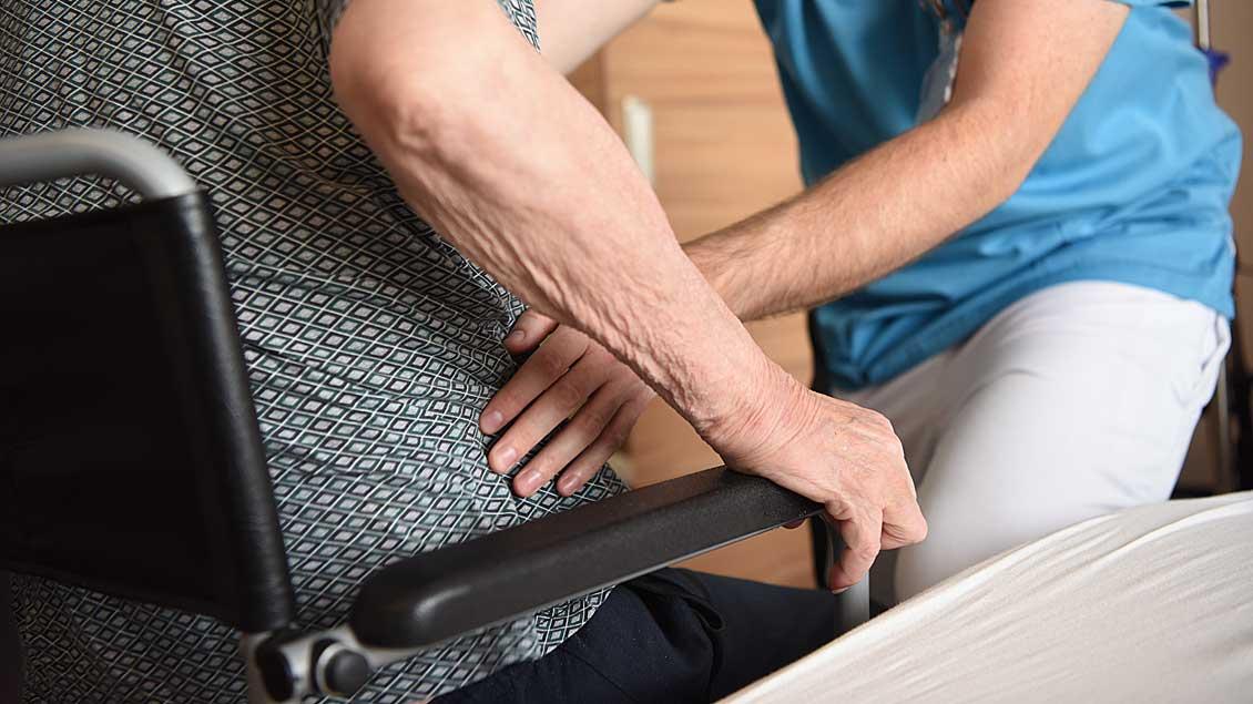 Pfleger hilft altem Mann aus dem Rollstuhl.