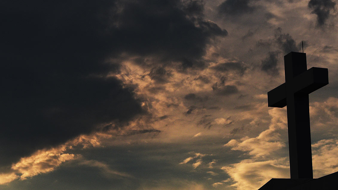 Kreuz vor dunklen Wolken
