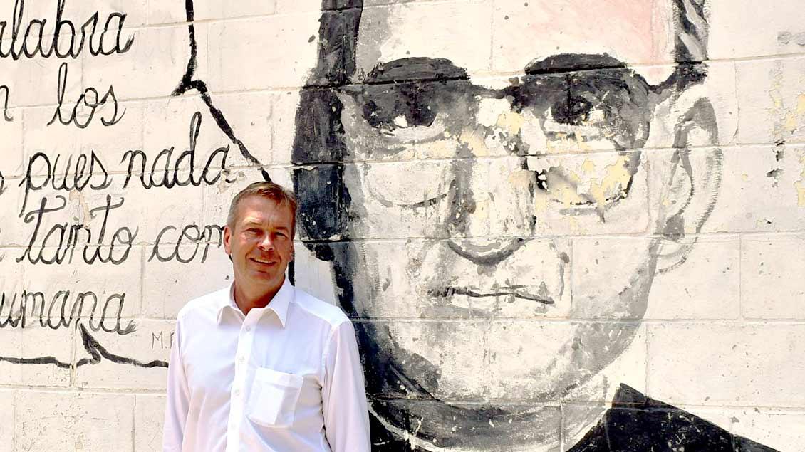 Bernd Finke, Botschafter der Bundesrepublik Deutschland in El Salvador, vor einem Mauerporträt des 1980 erschossenen Erzbischofs von San Salvador, Oscar Romero. Am 14. Oktober 2018 spricht in Papst Franziskus in Rom heilig.