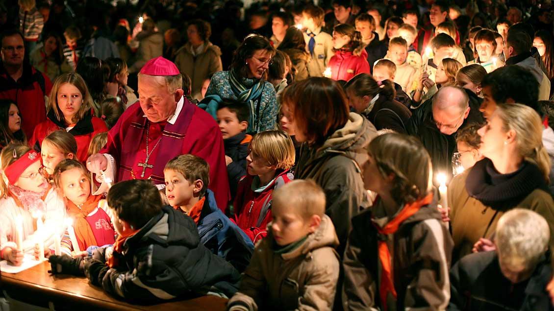 Weihbischof Friedrich Ostermann mit Kindern beim Empfang des Friedenslichts aus Bethlehem im Münsteraner Dom.