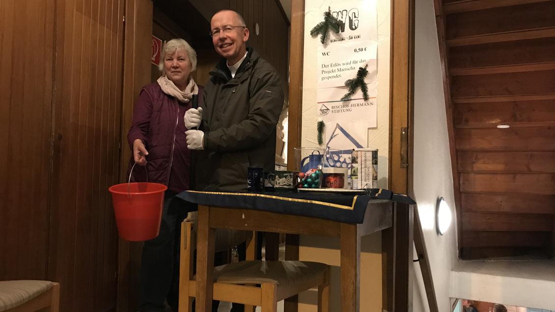 Gertrud Barlag von der katholischen Frauengemeinschaft und Pfarrer Peter Kossen putzen die Toiletten auf dem Weihnachtsmarkt in Leeden.