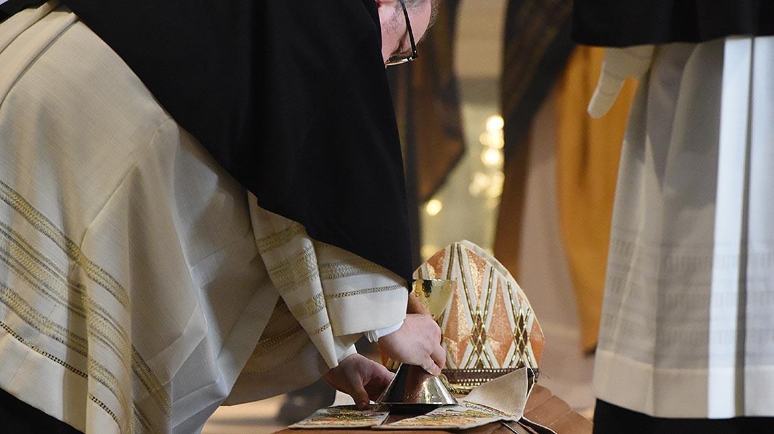 Kelch und Mitra von Weihbischof Ostermann werden auf seinen Sarg gelegt. | Foto: Michael Bönte