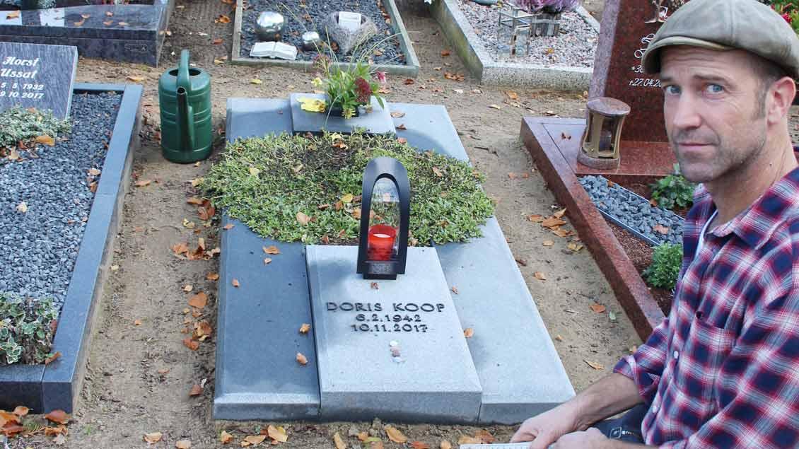 Rainer Kuehn zeigt das Grab, das er umgestalten muss. Die Gestaltung verstößt gegen die Friedhofssatzung der Pfarrei, die am 1. Januar 2016 in Kraft getreten ist.
