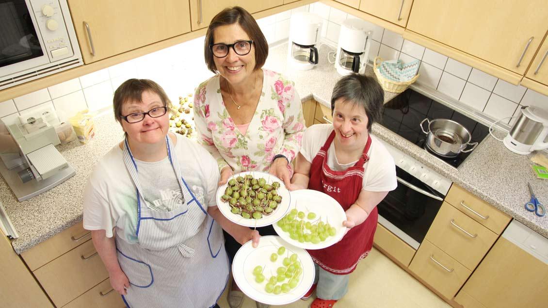 Servieren Traubenspieße mit Schokolade und Liebesperlen (von links): Edith Ameling, Marie Bolsen und Birgitt Maßmann. Foto: Michel Hülskemper (Haus Hall)