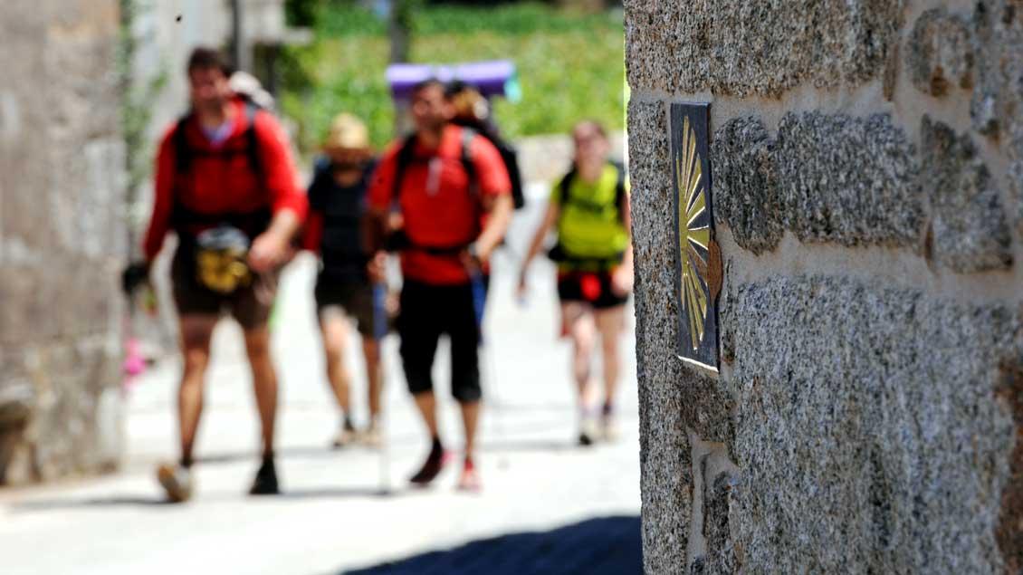 Pilger auf dem spanischen Jakobsweg, rechts an der Mauer die Muschel als Zeichen der Jakobspilger.